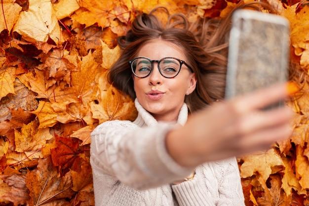 Grappige schattig gelukkig jonge vrouw hipster in stijlvolle bril in een gebreide trui fotografeert zichzelf op een mobiele telefoon. moderne vrij vrolijke meisje maakt een selfie liggend op herfst oranje gebladerte in een park.