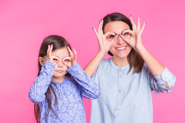 Grappige schattige dochter en moeder die glazen met vingers voor de gek houden.