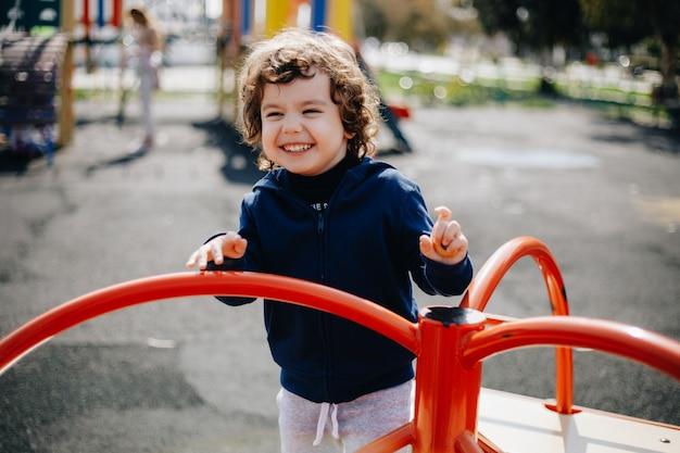 Grappige schattige gelukkig baby spelen op de speelplaats. de emotie van geluk, plezier, vreugde. glimlach van een kind.