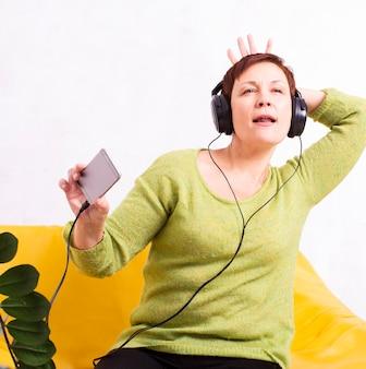 Grappige senior vrouw luisteren muziek op koptelefoon