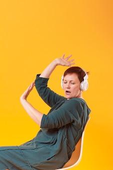Grappige senior vrouw luisteren muziek