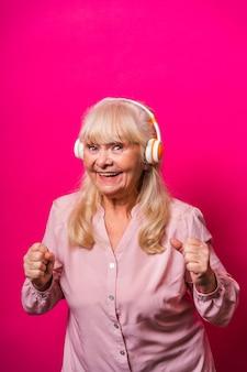 Grappige senior vrouw luistert muziek met een koptelefoon