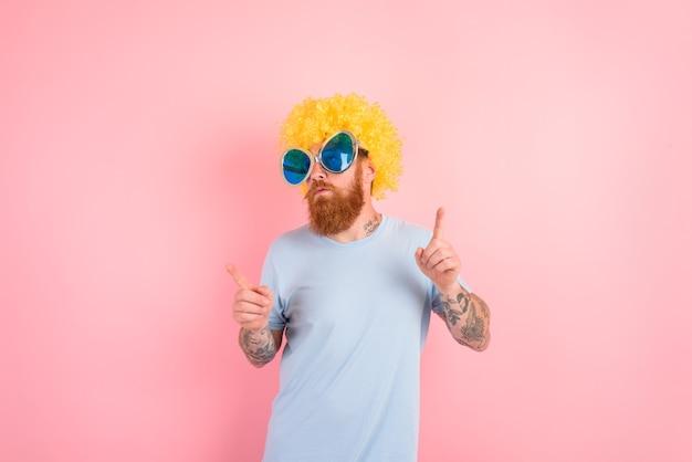 Grappige serieuze man met peruk en zonnebril dansen