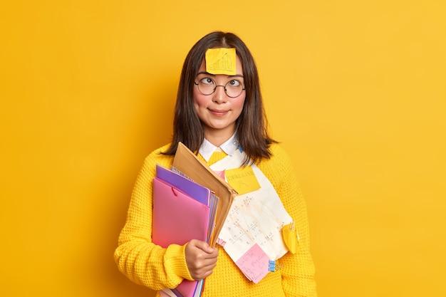 Grappige slimme vrouwelijke nerd kruist ogen heeft sticker met getekende afbeelding op voorhoofd