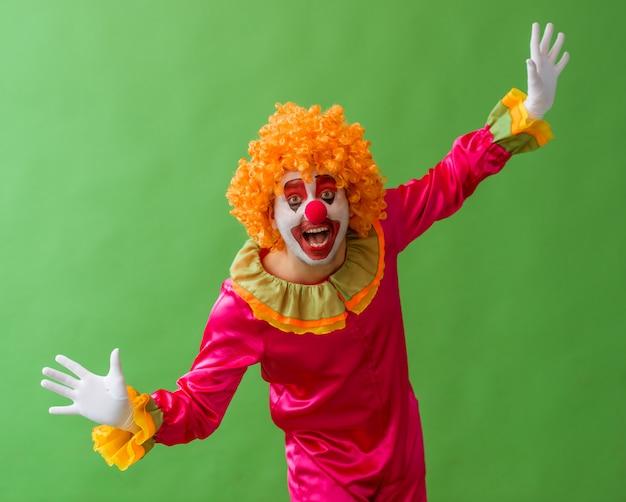 Grappige speelse clown in oranje pruik die handen apart houdt.
