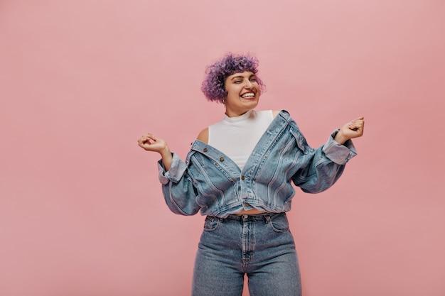 Grappige stijlvolle dame met sneeuwwitte glimlach heeft plezier op roze. vrouw in jeans strakke broek.