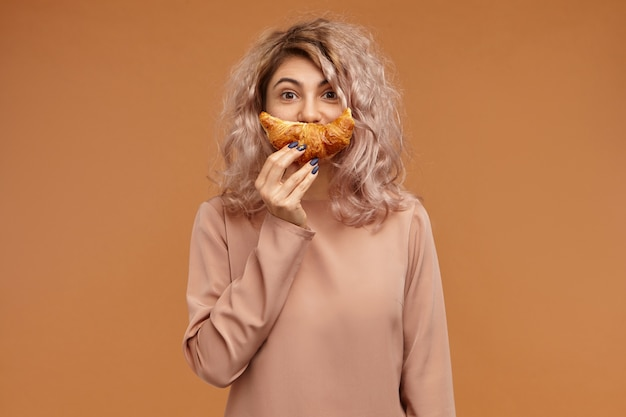 Grappige stijlvolle jonge vrouw in top met lange mouwen gek rond tegen lege oranje muurruimte, vers gebakken croissant over haar gezicht te houden