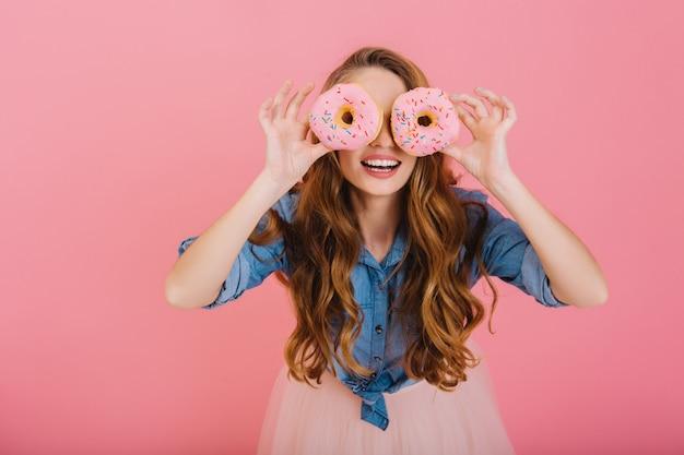 Grappige stijlvolle meid in trendy outfit dwazen rond met heerlijke donuts die ze bij de bakkerij kocht voor thee. portret van bevallige krullende jonge vrouw poseren met snoep geïsoleerd op roze achtergrond