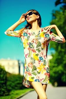 Grappige stijlvolle sexy lachende mooie jonge vrouw model in zomer heldere hipster doek jurk in de straat