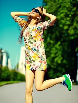 Grappige stijlvolle sexy lachende mooie jonge vrouw model in zomer heldere hipster doek jurk springen in de straat