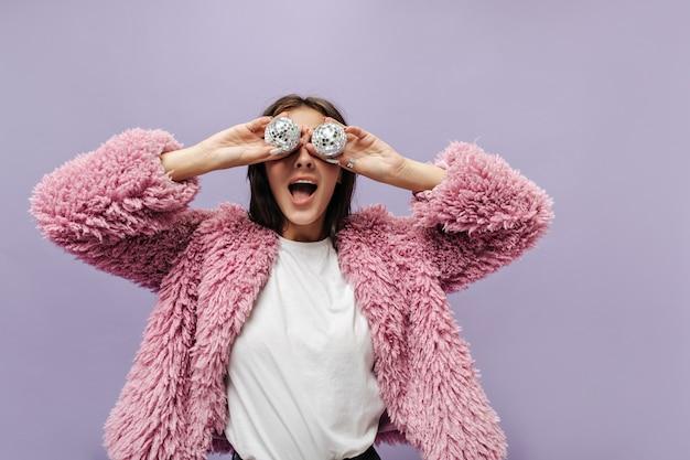 Grappige stijlvolle vrouw in cool t-shirt en modieuze roze pluizige trui poseren met discoballen op geïsoleerde lila muur