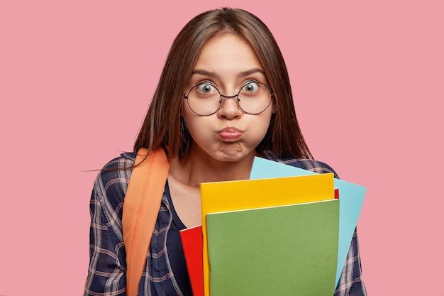 Grappige student poseren tegen de roze muur met bril