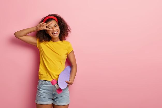 Grappige tiener met krullend haar poseren in gele t-shirt