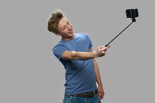 Grappige tienerjongen die selfiestick gebruikt. stijlvolle tiener kerel die selfi met monopod tegen een grijze achtergrond. jeugd en modern technologieconcept.