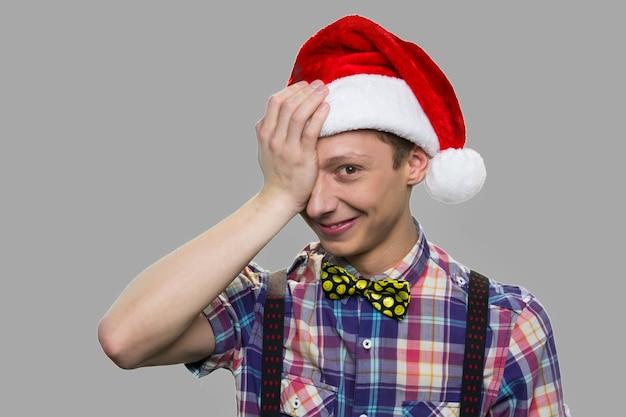 Grappige tienerjongen in kerstmanhoed. mooi jong geitje dat in kerstmishoed één oog behandelt met hand tegen grijze achtergrond. mensen en wintervakantie concept.