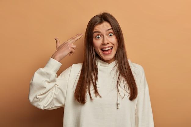 Grappige tienermeisje dwazen rond, schiet in de tempel, doet alsof ze zelfmoord pleegt, heeft een vrolijke uitdrukking, draagt een wit sweatshirt