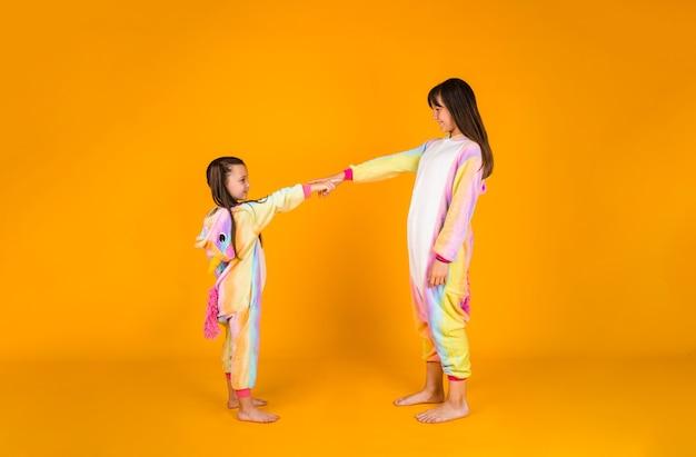 Grappige twee meisjes in pluche pyjama's staan op een gele achtergrond met een plek voor tekst