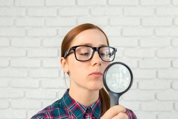 Grappige uitdrukking. geschokte vrouw die door een vergrootglas kijkt.