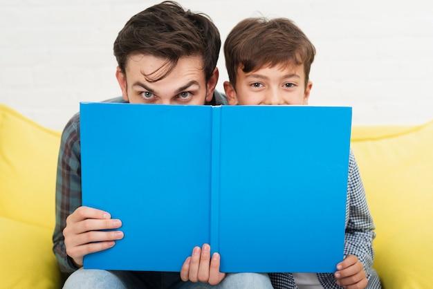 Grappige vader en zoon die hun gezichten bedekken