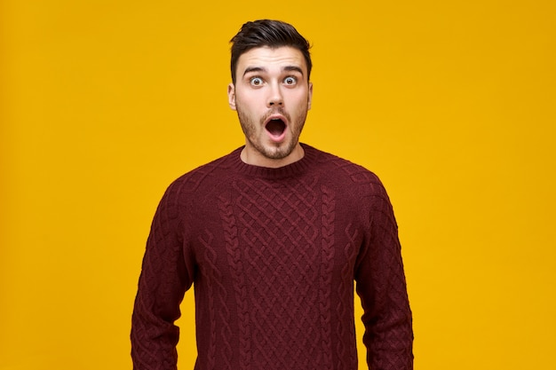Grappige verbaasde jonge man met een paniekerige blik, bang om te laat te komen voor de verkoop, zijn mond wijd open te houden, kan zijn eigen ogen niet geloven