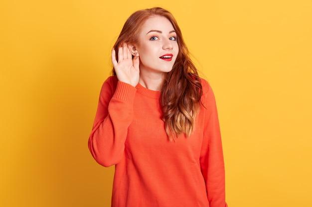 Grappige verbaasde roodharige europese vrouw, die wenkbrauwen optrekt, verbazing uitdrukt, hand bij het oor houdt en probeert naar roddels te luisteren