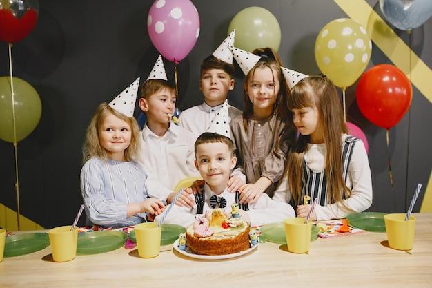 Grappige verjaardagsfeestje voor kinderen in ingerichte kamer. gelukkige jonge geitjes met cake en ballons.