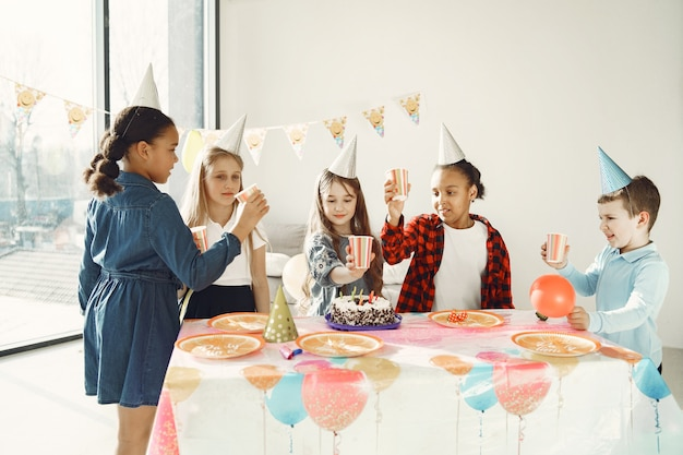 Grappige verjaardagsfeestje voor kinderen in ingerichte kamer. gelukkige kinderen met cake en ballons.