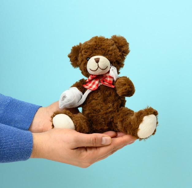 Grappige vintage bruine krullende teddybeer met teruggespoelde poot met wit gaasverband, concept van verwondingen bij kinderen of dieren