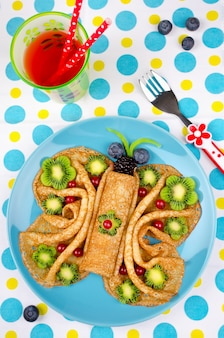 Grappige vlindergezichtspannenkoekjes met bessen en fruit voor snacks voor kinderen