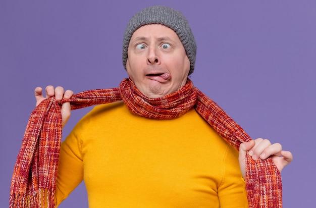 Grappige volwassen slavische man met wintermuts en sjaal om zijn nek die zijn tong uitsteekt en zichzelf verstikt met sjaal