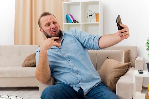 Grappige volwassen slavische man zit op fauteuil kijken naar telefoon selfie te nemen in de woonkamer