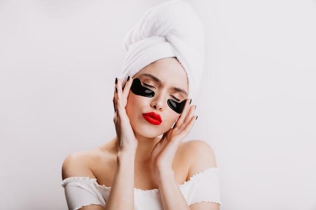 Grappige volwassen vrouw in handdoek hydrateert de huid onder de ogen vóór make-up. dame met rode lippenstift vormt met gesloten ogen op witte muur.