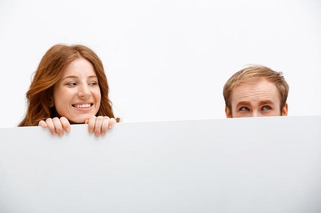 Grappige volwassenen roodharige man en vrouw verstopt achter tafel