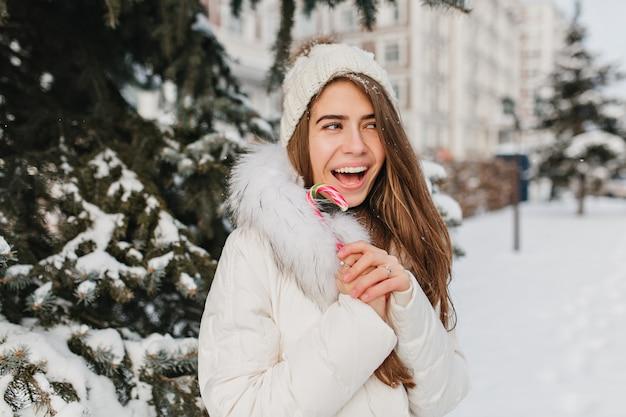 Grappige vreugdevolle winter vrouw met lolly in stad. plezier hebben in de sneeuw, gekke bui, glimlachen, positieve heldere emoties. nieuwjaar komt eraan, koud weer, gelukkige tijd.