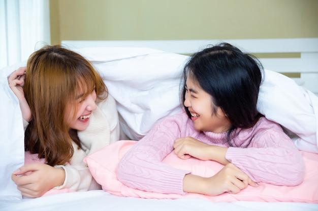 Grappige vrienden liggen onder deken met kussens op bed