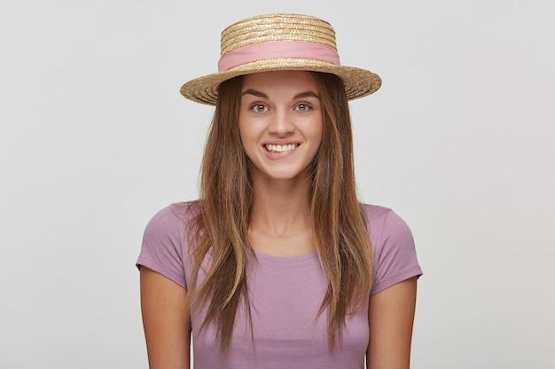 Grappige vrolijke blije jonge vrouw in een strohoed met een roze lint, ziet er speels uit