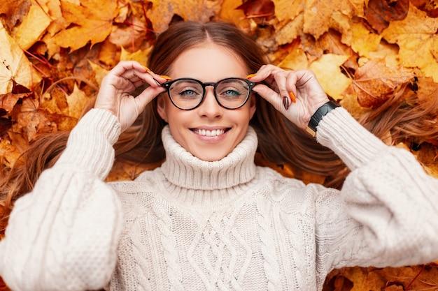 Grappige vrolijke jonge hipster vrouw in een warme gebreide trui maakt modieuze glazen recht. vrolijk meisje met een positieve glimlach rust liggend op de oranje bladeren in het park. gelukkige herfstdag.