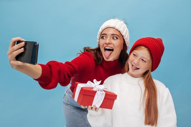 Grappige vrolijke jonge vrouwen in stijlvolle kleding tonen tongen op blauwe muur