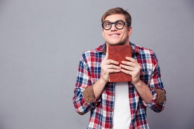 Grappige vrolijke jongeman in ronde bril en geruit hemd met boek over grijze muur