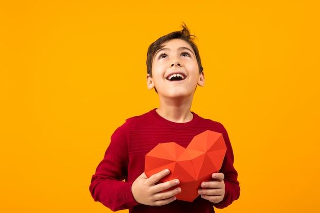 Grappige vrolijke knappe kaukasische jongen met papier hart voor valentijnsdag op oranje