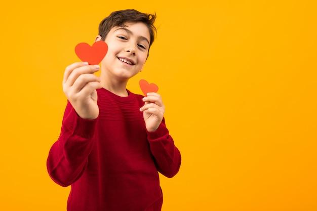 Grappige vrolijke knappe kaukasische jongen met papieren kaarten in de vorm van harten voor valentijnsdag onn oranje