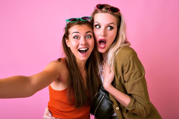 Grappige vrolijke vrouw maakt samen selfie, trekt grimassen en toont lange tongen
