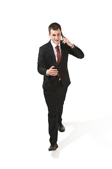 Grappige vrolijke zakenman die met mobiele telefoon over wit gaat.