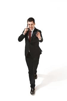 Grappige vrolijke zakenman die met mobiele telefoon over witte studio gaat