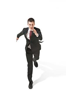Grappige vrolijke zakenman die met mobiele telefoon over witte studio loopt