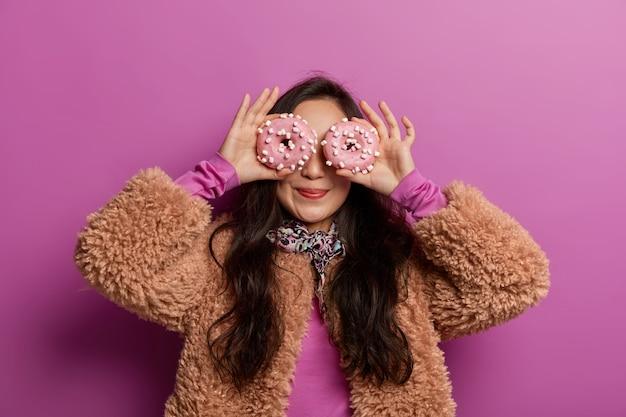 Grappige vrouw bedekt ogen met versierde donuts als bril, lacht aangenaam, gekleed in winterkleding, heeft plezier met desserts