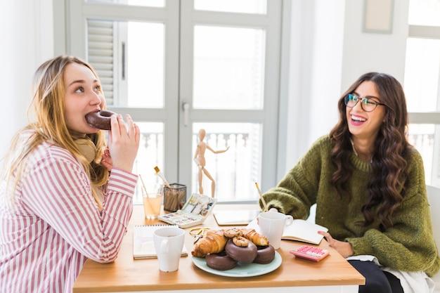 Grappige vrouw die donuts en tekening eet
