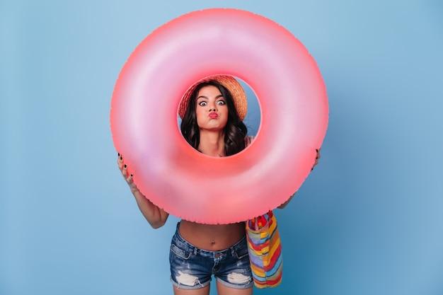 Grappige vrouw die in denimborrels roze zwemmende cirkel houdt