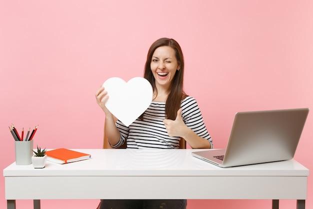 Grappige vrouw die knippert met duim omhoog en houdt een wit hart vast met kopieerruimte die aan een project werkt terwijl ze op kantoor zit met een laptop