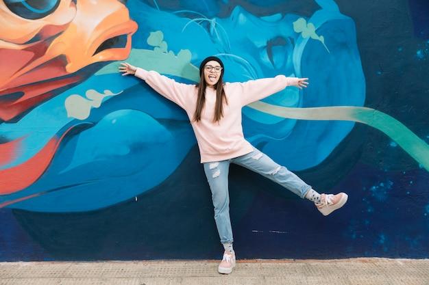 Grappige vrouw die zich voor graffitimuur bevindt